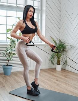 Кавказская мускулистая женщина средних лет в спортивной одежде позирует на коврике, работая с резинками в комнате.