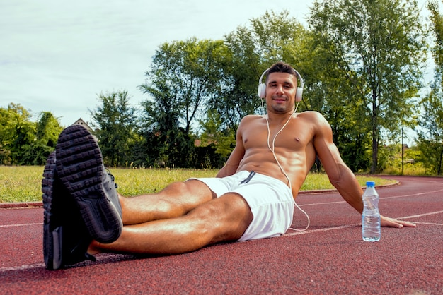 Caucasian muscular shirtless fitness man sitting on the ground and listening to a music