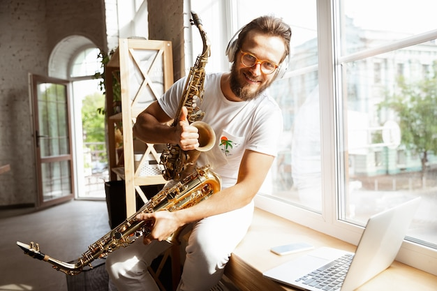 Кавказский музыкант мужчина во время онлайн-концерта дома изолирован и находится на карантине,