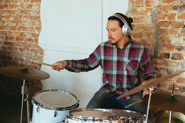 집에서 온라인 콘서트 중 drumms를 연주하는 백인 음악가 격리 및 격리. 카메라, 노트북, 스트리밍, 녹화 과정을 사용합니다. 예술, 지원, 음악, 취미, 교육의 개념.