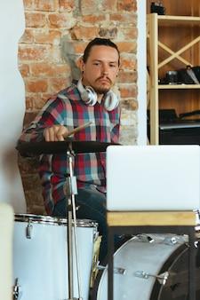 隔離され隔離された自宅でのオンラインコンサート中にドラムを演奏する白人のミュージシャン。