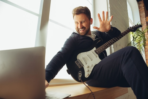 집에서 온라인 콘서트 도중 기타를 연주하는 백인 음악가