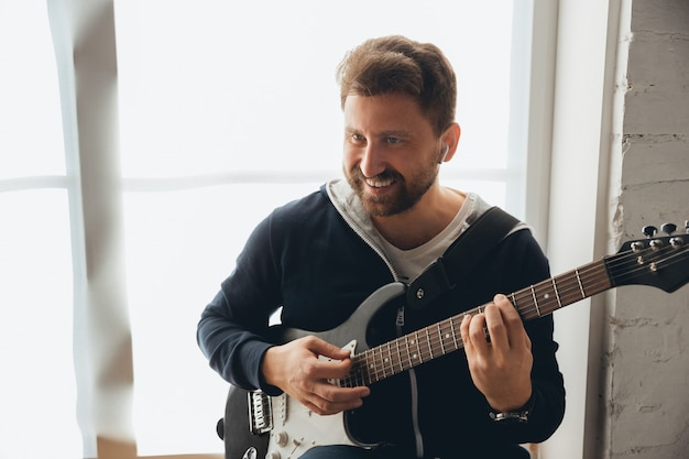 Caucasian musician playing guitar during online concert at home isolated and quarantined, cheerful improvising