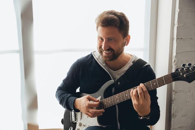 Musicista caucasico suonare la chitarra durante il concerto online a casa isolato e messo in quarantena, improvvisazione allegra