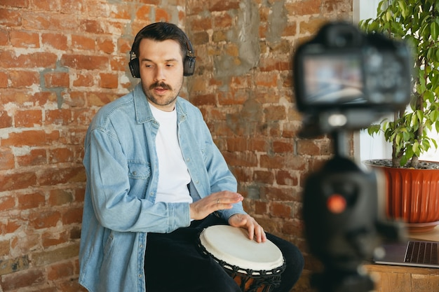 Caucasian musician playing hand drum during online concert at home isolated and quarantined. using camera, laptop, streaming, recording courses. concept of art, support, music, hobby, education.