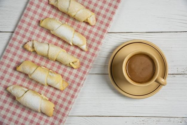 Il mutaki caucasico su un tovagliolo controllato rosso è servito con una tazza di cioccolata calda