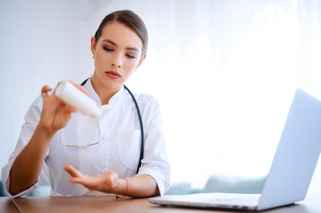 Кавказская медсестра наносит дезинфицирующее средство в больнице во время карантина. врач с антисептиком