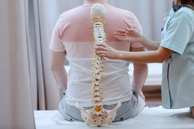Caucasian nurse holding spine model against the patients backs. clinic interior.