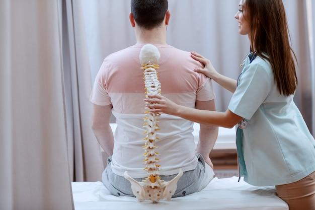 患者の背中に対して背骨モデルを保持している白人の看護師。クリニックのインテリア。