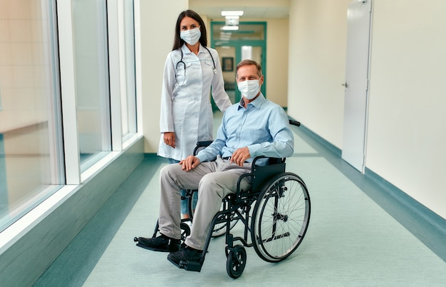 Caucasian nurse taking care of a mature male patient sitting in a wheelchair at the hospital. young woman and old man wearing surgical mask to protect against covid 19 pandemic.