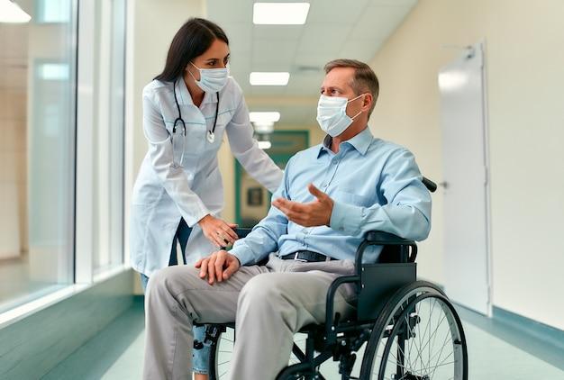 병원에서 휠체어에 앉아 성숙한 남성 환자를 돌보는 백인 간호사.