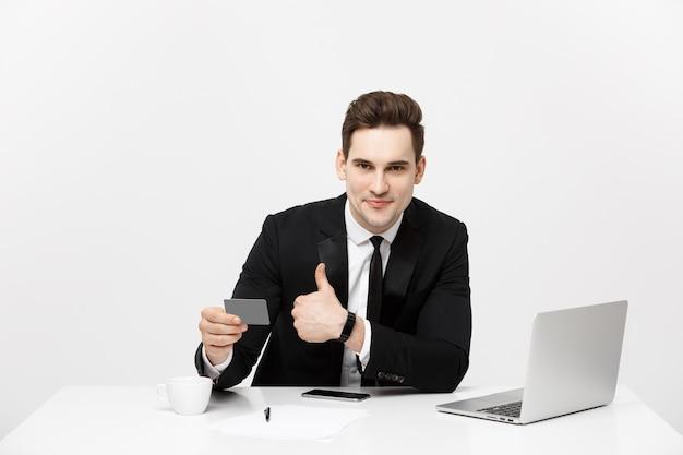 フォーマルなスーツとネクタイを着た白人のオフィスマンが、プラスチック製のクレジットカードでデジタルマネーをデモンストレーションしています...