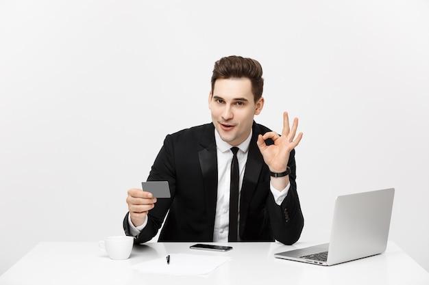 フォーマルなスーツとネクタイを着た白人のオフィスマンが、プラスチック製のクレジットカードでデジタルマネーを示し、灰色の背景に分離されたokを示しています。