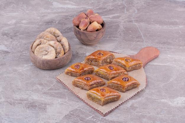 乾いたイチジクとナツメヤシと木製の大皿に白人のパクラヴァ。