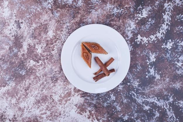 Кавказская пахлава с палочками корицы в белой тарелке в центре. фото высокого качества