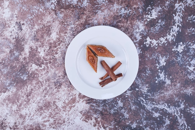 Caucasian pakhlava with cinnamon sticks in a white plate in the center. high quality photo