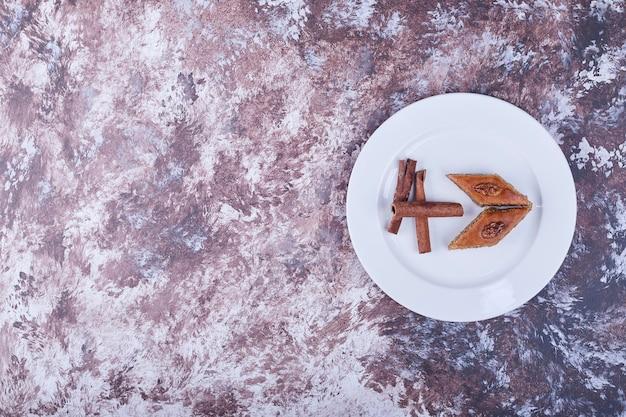 Pakhlava caucasico con bastoncini di cannella in un piatto bianco. foto di alta qualità