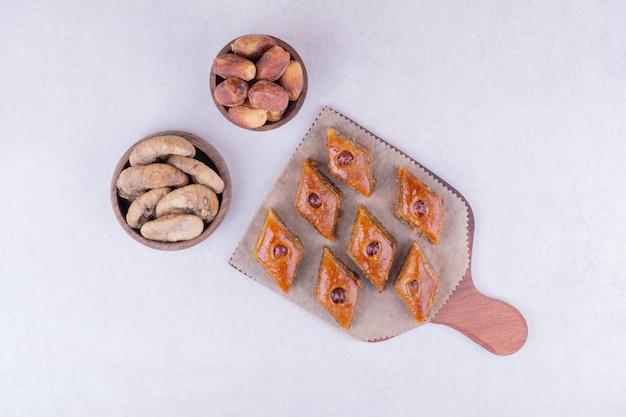 Pakhlava caucasico sul piatto di legno con fichi secchi e datteri.