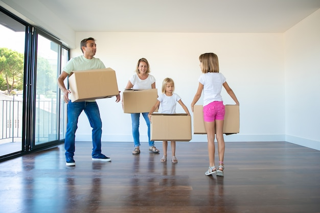 Caucasian parents and two girls holding carton boxes and standing in empty living room