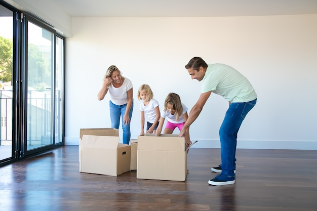 Caucasian parents unpacking cardboard boxes with daughters in empty room with balcony