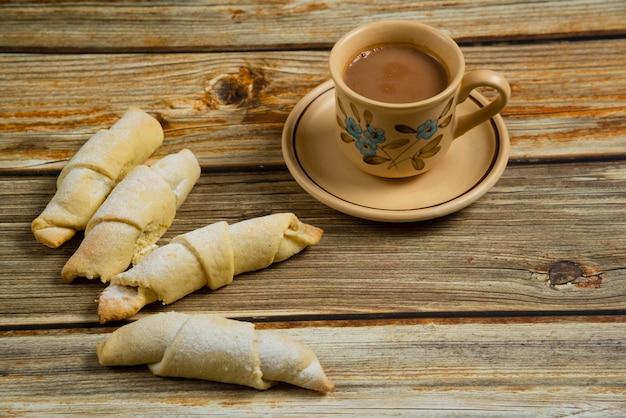 一杯のコーヒーと木製のテーブルの上の白人菓子ムタキ