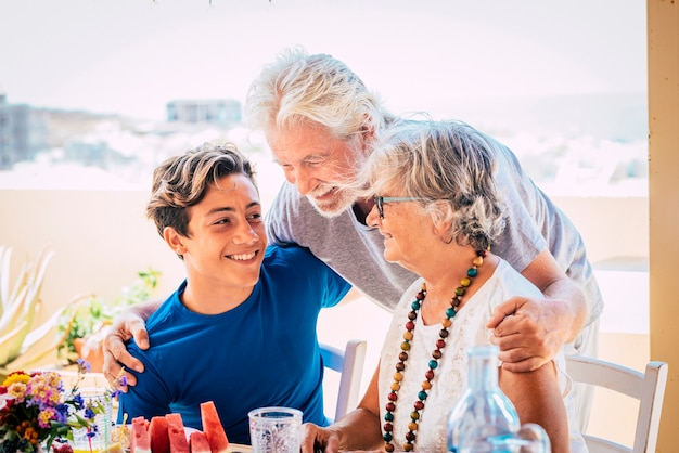 Caucasian people mixed ages and generations - grandfathers and grandson together family at the table eating food and enjoying friendship - happy old and young beautiful persons