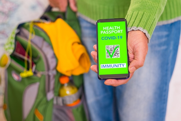 Caucasian people shows health passport of immunity for people vaccinated of coronavirus covid-19. holding backpack ready for travel