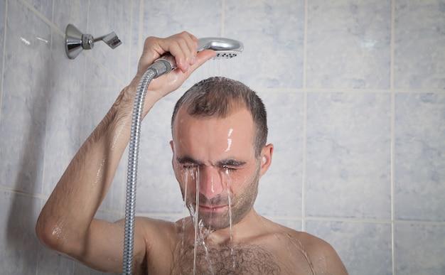 Кавказский человек в ванной. человек принимает душ