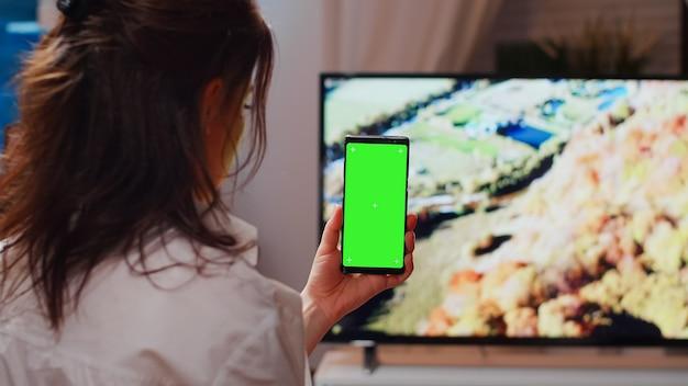 スマートフォンで緑色の画面を垂直に保持している白人