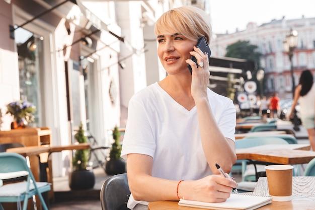 ノートに書き留めて携帯電話で話している間、通りのカフェに座っている白いtシャツを着ている白人の喜んでいる女性
