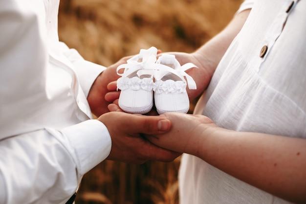 아기를 기대하는 백인 통통한 여자는 아이들을위한 신발 한 켤레를 들고 그녀의 연인 근처에 포즈입니다