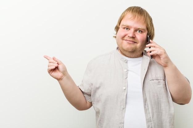 白人のプラスのサイズの男性が離れて人差し指で元気に指している笑顔で電話で呼び出します。
