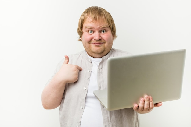 Caucasian plus size man holding a laptop surprised pointing at himself, smiling broadly.