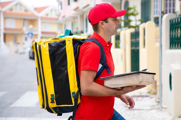 Caucasian postman holding parcel and delivering order. side view of deliveryman in red cap and shirt going to house of recipient.