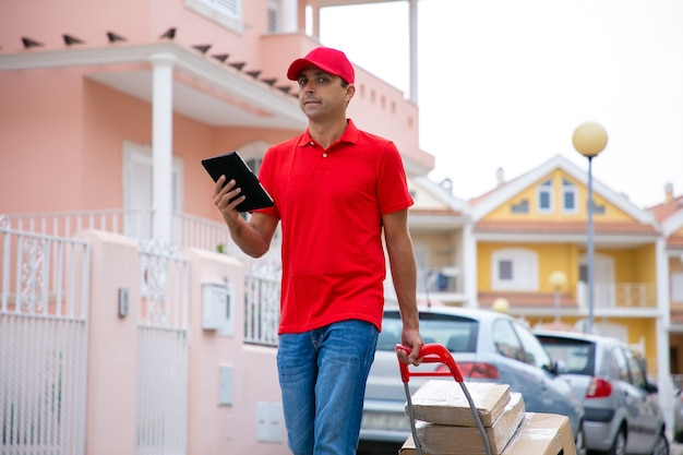 Caucasian postman holding tablet and handle of trolley with cardboard boxes. confident deliveryman in red uniform doing his job and delivering order on foot. delivery service and post concept