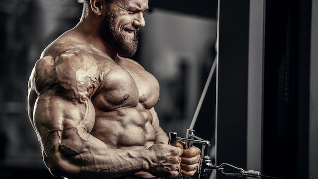Caucasian power athletic man training pumping up biceps muscles. strong bodybuilder