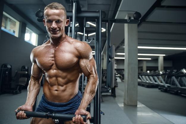 Кавказский силовой спортивный мужчина тренируется, накачивая мышцы бицепса