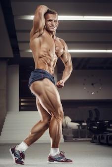 脚の大腿四頭筋をポンピングする白人パワーアスレチックマントレーニング。 6パック、完璧な腹筋、上腕三頭筋、胸、ジムの肩を備えた強力なボディービルダー。フィットネスとボディービルのコンセプト