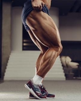 Кавказский силовой спортивный человек, накачивающий четырехглавые мышцы ног.