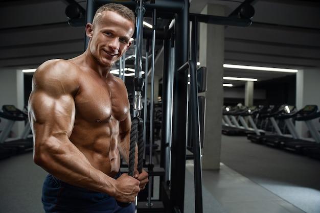 Кавказский силовой спортивный мужчина тренируется, накачивая мышцы трицепса