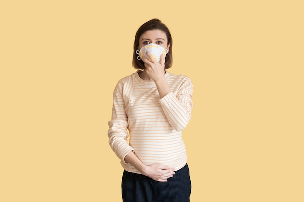 Caucasian pregnant mother is wearing a medical mask posing on a yellow wall