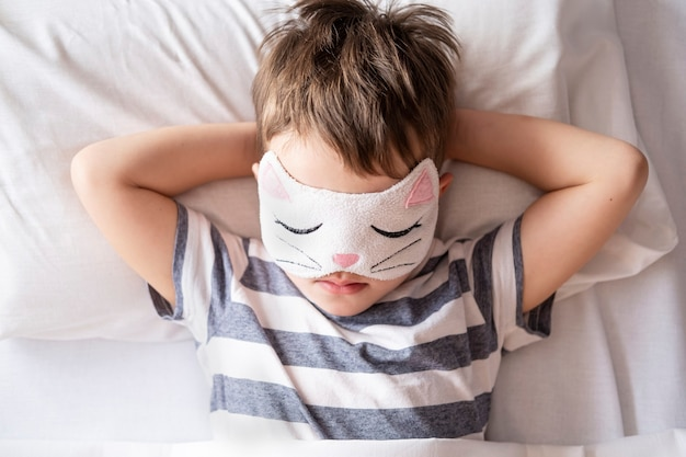 Кавказский дошкольник в полосатой пижаме с маской для глаз котенка, лежащей в белой кровати.