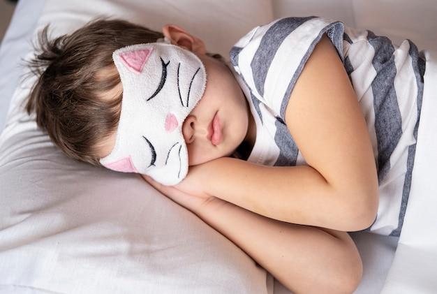 Кавказский дошкольник в полосатой пижаме с маской для глаз котенка спит в белой кровати.
