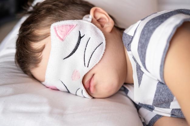 Caucasian preschool boy in kitty eye mask striped pyjamas sleep in white bed.
