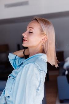 Кавказская довольно блондинка с короткими волосами женщина в джинсовой куртке расчесывает волосы розовой расческой дома