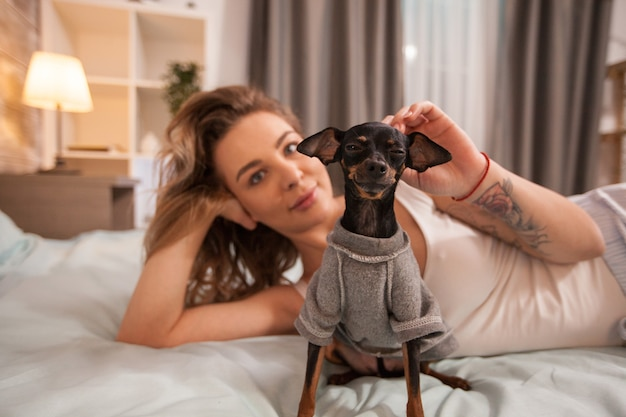 Caucasian pretty woman relaxing in bed wearing pajamas while playing with her little dog.