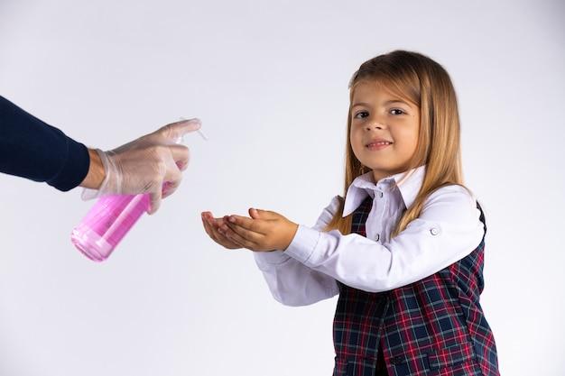 학교 제복을 입은 백인 초등학교 여학생은 흰 벽에 고립 된 교실에 들어가기 전에 그녀의 손을 소독합니다.