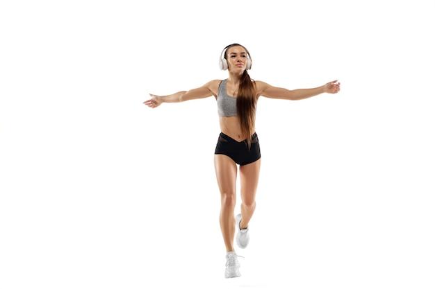 白人のプロの女性ランナー、白いスタジオの背景に分離されたアスリートトレーニング。