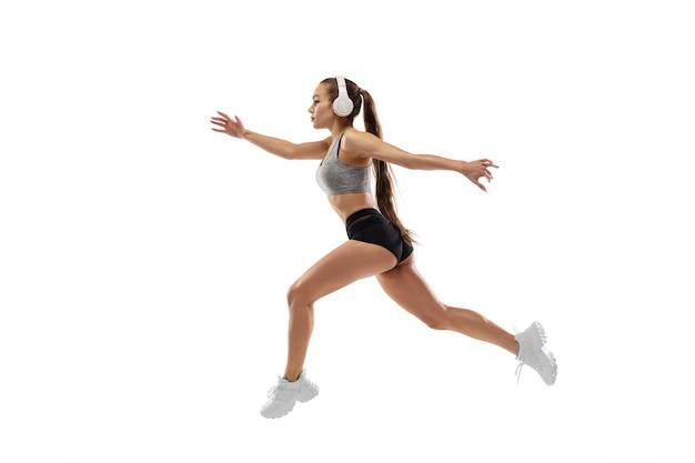 白人のプロの女性ランナー、白いスタジオで隔離のアスリートトレーニング