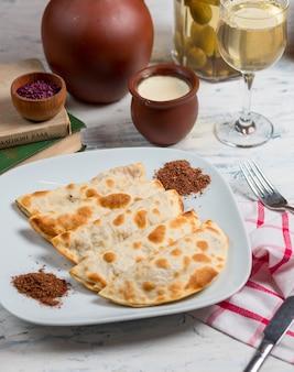Caucasian qutab, kutab, gozleme served with sumakh, herbs and yogurt.